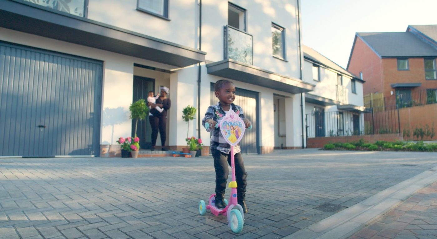 Child on Scooter in Front of House
