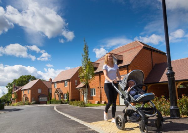 Woman pushing Pushchair outside Drew Smith Homes